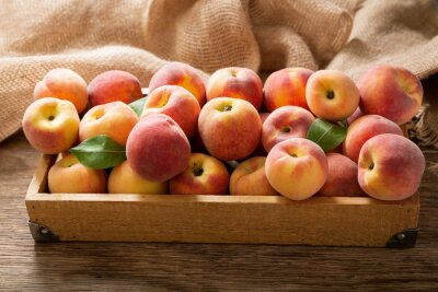 fresh ripe peaches with leaves in a wooden box