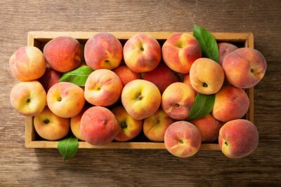 fresh ripe peaches with leaves in a wooden box, top view