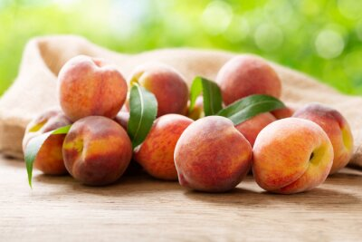 fresh ripe peaches with leaves on a wooden table