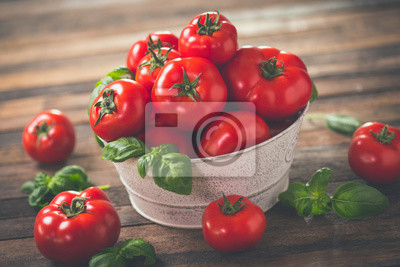 Fresh ripe tomatoes and basil on the wooden table