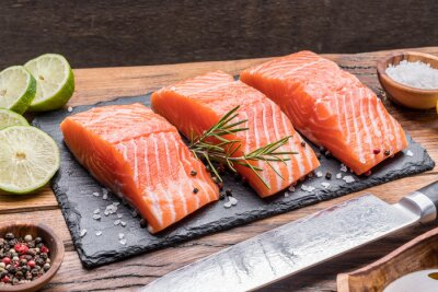 Fresh salmon fillets on black cutting board with herbs and spices.