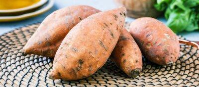 Papiers peints Fresh sweet potatoes on rustic background.