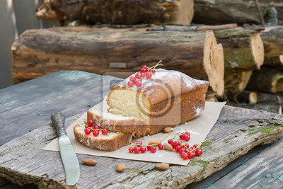 Fruit cake with red currant and almond on a garden table