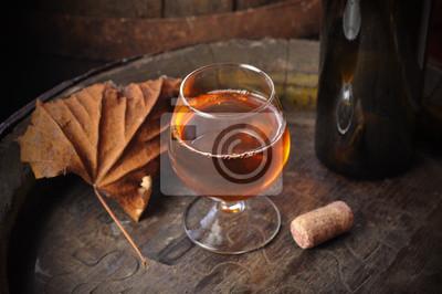 Glass of cognac on the vintage wooden barrel