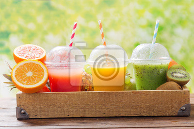 glasses of fruit juice and smoothie with fresh fruits