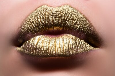 Papiers peints Gold lips. Woman wouth close up with golden color lipstick on lip. Glitter glossy lips biting.