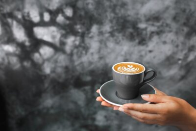 Papiers peints Gray cup of fresh cappuccino in woman hands on background of gray concrete cement textured wall. Trendy hipster cafe design.