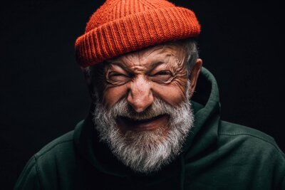 Papiers peints Grey- haired aged grandfather feeling overjoyed and excited while telling about his trip to mountains. Old man dressed in red knitted hat and green hoodie. Happy to be active in retirement