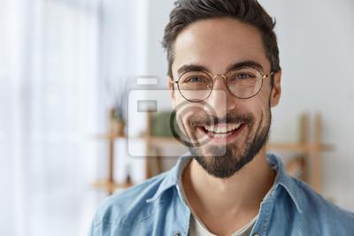 Papiers peints Gros coup de joyeux satisfait mâle attrayant avec chaume, a un large sourire, porte des lunettes rondes, se réjouit du succès au travail, se dresse contre un intérieur confortable. Designer à la mode