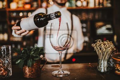 Papiers peints Gros plan d'un barman versant du vin rouge dans un verre. Concept d'accueil, de boissons et de vin.