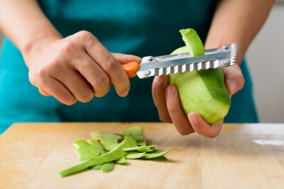 Hand holding knife and peeled green mango preparing for salad