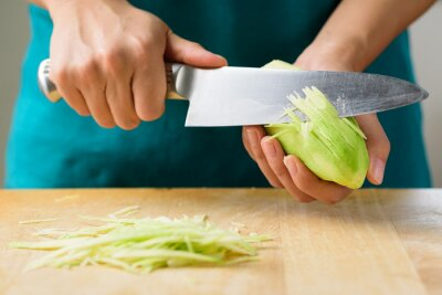 Hand holding knife and sliced green mango preparing for salad