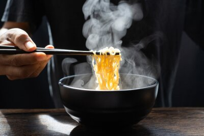 Papiers peints Hand uses chopsticks to pickup tasty noodles with steam and smoke in bowl on wooden background, selective focus. Asian meal on a table, hot food and junk food concept