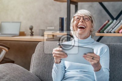 Papiers peints Happy senior woman looking and laughing at her digital tablet on sofa