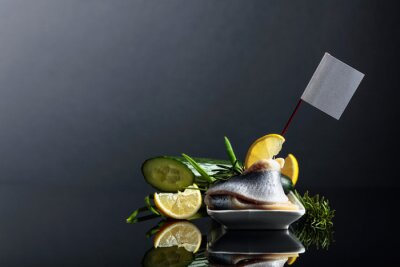 Herring fillet with lemon, green cucumber, onion and rosemary. Sandwich with herring fillet in oil.