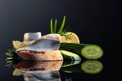 Herring with lemon, green cucumber, onion and rosemary.