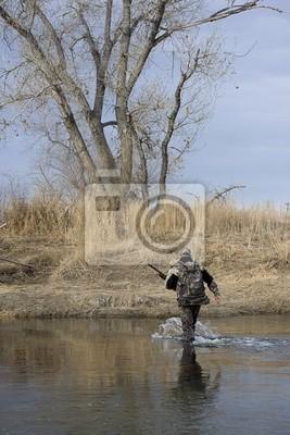 Papiers peints Hunter dans des tissus de camouflage avec un fusil traversant une rivière