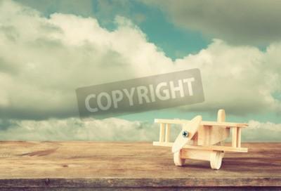 Papiers peints Image d'un avion de jouet en bois sur une table en bois contre le ciel nuageux. Image de style rétro