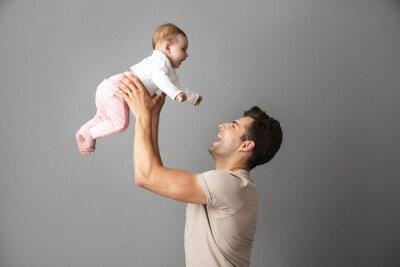Papiers peints Image d'un homme heureux père tenant son petit enfant dans les mains, isolé sur fond gris