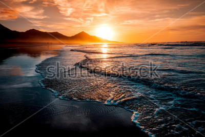 Papiers peints Incroyable coucher de soleil sur la plage avec un horizon sans fin et des silhouettes solitaires au loin et des vagues incroyablement mousseuses. Les collines volcaniques en arrière-plan dans des coul
