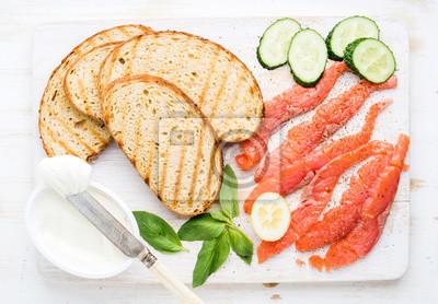 Ingrédients pour un sandwich sain Tranches de pain grillé, saumon fumé, fromage cottage, basilic concombre sur fond blanc, vue de dessus