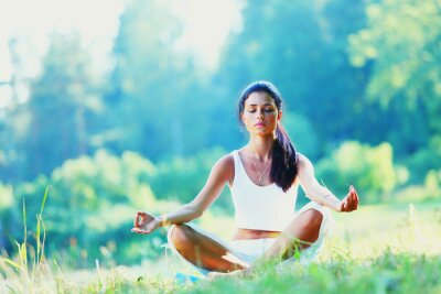 Papiers peints Jeune femme faisant l'exercice de yoga dans le parc verdoyant