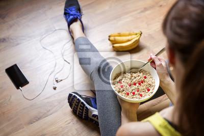 Papiers peints Jeune fille mangeant une farine d'avoine avec des baies après une séance d'entraînement. Fitness et concept de mode de vie sain.