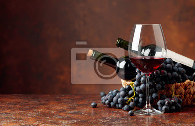 Papiers peints Juicy blue grapes and bottles of red wine on a brown background.