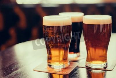 Papiers peints Lunettes de la bière claire et foncée sur un fond de pub.