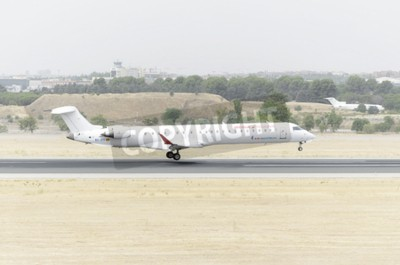 Papiers peints MADRID, SPAIN - AUGUST 8th 2015: Aircraft -Bombardier Canadair CRJ-900-, of -Air Nostrum- airline, is landing on Madrid-Barajas -Adolfo Suarez- airport, on August 8th 2015.