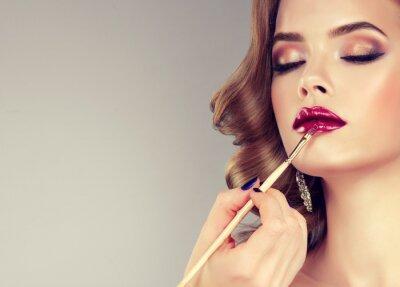 Papiers peints Main de maquillage maître, peinture des lèvres de jeune modèle belle. Maquillage en cours.