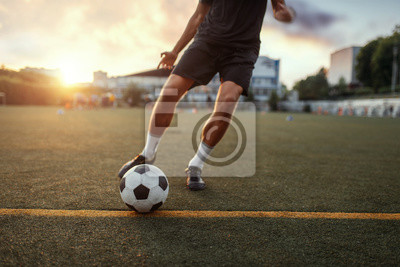Papiers peints Male football player hits the ball on the field