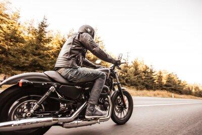 Papiers peints Man siège sur la moto sur la route dans la forêt.