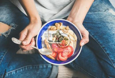 Papiers peints Manger, petit déjeuner, bol Yogourt, granola, graines, fruits frais et secs et miel dans un bol de céramique bleue dans les mains de la femme. Propre, manger, régime, désintoxication, végétarien, nour