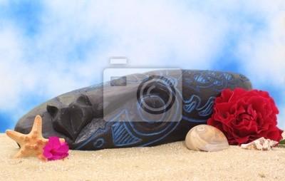 Masque en bois sur le sable avec des fleurs et fond de ciel bleu