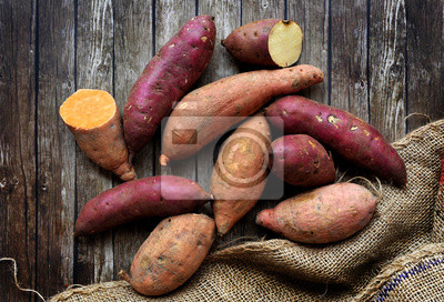 Papiers peints Mélange de patates douces avec le sac sur fond en bois