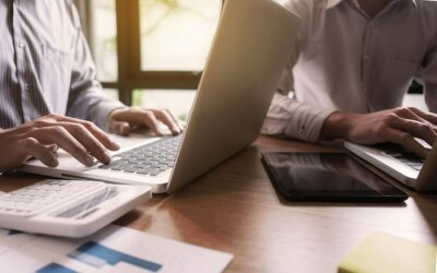 Papiers peints Midsection Of Business Colleagues Using Laptops On Wooden Table In Office