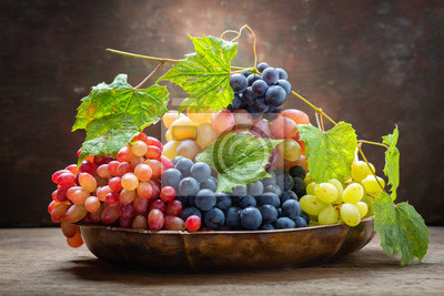 mix of fresh ripe grapes with leaves in a bowl