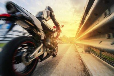 Papiers peints Moto da strada sfreccia vicino al rambarde al tramonto