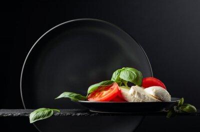 Mozzarella with tomato and basil on a black background.