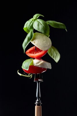 Mozzarella with tomato and basil on a fork.