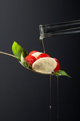 Mozzarella with tomato, basil and olive oil on a dark background.