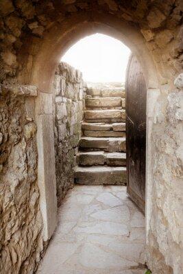 Papiers peints Mur de pierre avec porte et rayons de lumière derrière ouverte