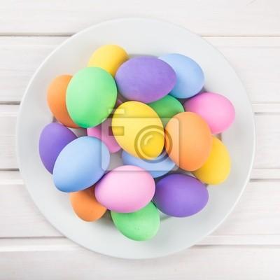 Oeufs de Pâques colorés pastel sur fond blanc bois