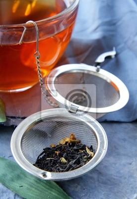 passoire à thé avec un thé noir parfumé et tasses