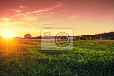 Papiers peints Paysage rural avec beau ciel du soir dégradé au coucher du soleil. Champ vert et village à l'horizon