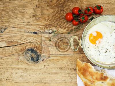 Petit-déjeuner ensemble: oeuf au plat, du pain et tomates-cerises sur un bois