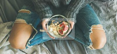 Papiers peints Petit-déjeuner sain d'hiver au lit. Femme en pull et jeans tenant la bouillie de riz de noix de coco avec des figues, des baies, des noisettes, vue de dessus, composition large. Alimentation propre, v