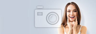 Papiers peints Photo of young toothy smiling woman showing smile, over grey background