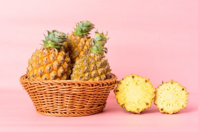 Pineapple fruit in a basket on pink background, Tropical fruit